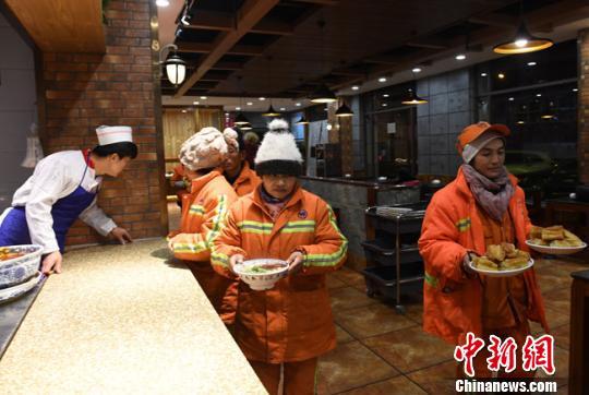 """在甘肃省会兰州,很多人的一天是从一碗牛肉面开始。然而对于已经在寒夜中清扫数个小时的环卫工人来说,一碗爱心牛肉面早餐更多的是让他们心里""""热乎""""了起来。图为环卫工人享用免费早餐。 杨艳敏 摄"""