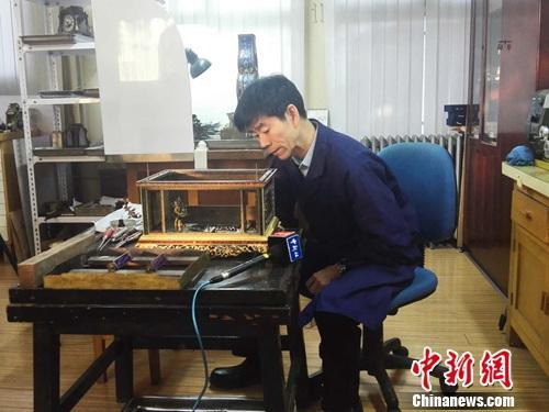 王津在检查待修复的钟表。