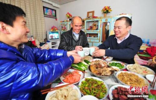 资料图:辽宁省葫芦岛市民在家中与家人享受丰盛的年夜饭。<a target='_blank'  data-cke-saved-href='http://www.chinanews.com/' href='http://www.chinanews.com/'><p  align=