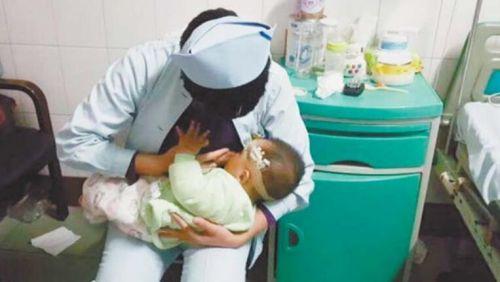 婴儿父母受重伤 护士病房里脱衣喂奶(图)