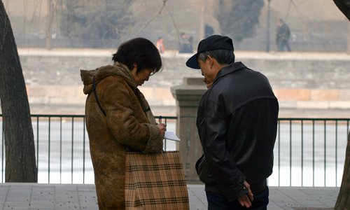 Two parents swap their children's information in Zhongshan Park in central Beijing. Photo: Li Hao/GT