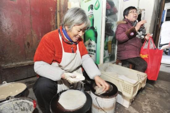 张福文(左)制作的春卷皮子备受老吃客的青睐。 □记者 徐志强 摄