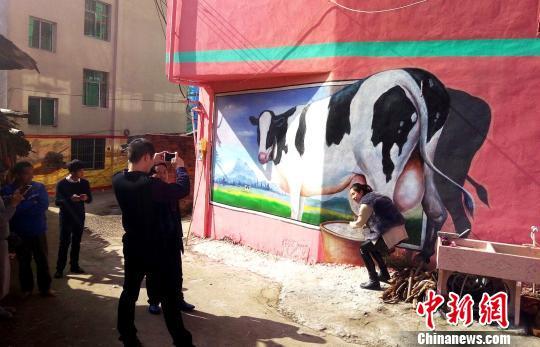 游客在奶牛画前留影。 吴苏梅 摄