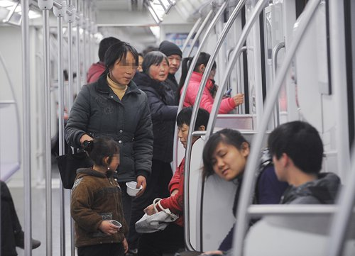 A child and her mother beg in a subway car in Shanghai on February 10, 2011. Photo: IC