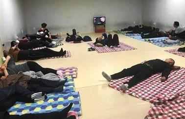 """中国侨网""""小黑屋""""内设施简陋,一间屋内同时铺上好几床被子,唯一家电是一个小电视机。本版图片/受访者供图"""