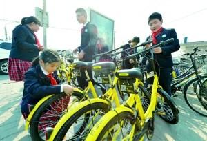 """日前,地坛小学的""""小雷锋""""们来到安定门地铁公交枢纽,将地铁口无序停放的共享单车整齐地摆好,方便行人取车。北京晨报记者 李木易/摄"""