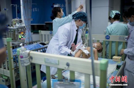 资料图片,医生小心翼翼地把患儿抱起来放到病床上。 李奇 摄