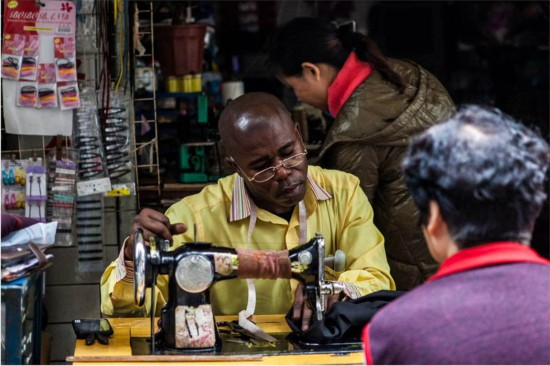Ted, an Angolan national, does some small business in Guangzhou. He has been in Guangzhou for almost four years and he has good relations with his neighbors. He borrowed the sewing machine from the shop owner for ten yuan each time. [Photo: People's Daily]