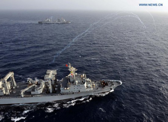 Ships of the 14th and the 15th Escort Taskforces of the Chinese Navy fire flares during the formation breaking ceremony in the Gulf of Aden, Aug. 26, 2013. [Photo: Xinhua]