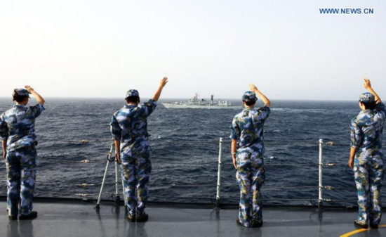 Soldiers on the Jinggangshan dock landing ship wave goodbye to the 14th Escort Taskforce of the Chinese Navy at the Gulf of Aden, Aug. 26, 2013. [Photo: Xinhua]