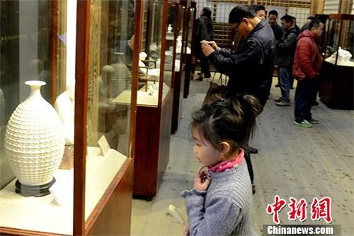 小观众正在欣赏陶瓷展览。中新社记者 刘可耕 摄