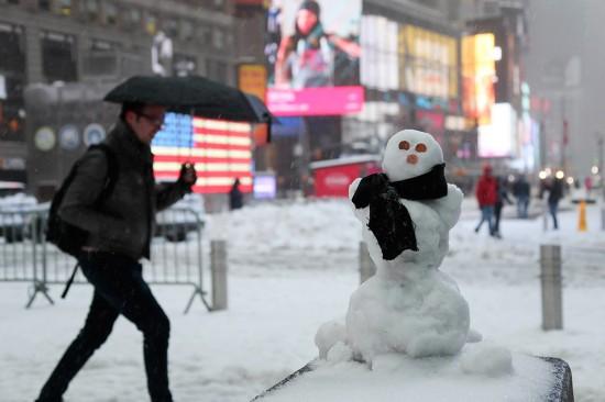 3月14日,一名男子从美国纽约时报广场的雪人旁走过。新华社记者 王迎 摄
