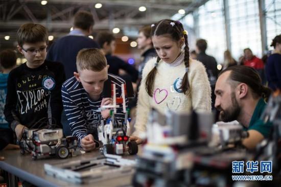 3月17日,在俄罗斯莫斯科,指导老师与参赛选手分析机器人出现的问题。当日,全俄机器人大赛在莫斯科举行。本次大赛共有超过5000名俄罗斯、白俄罗斯及哈萨克斯坦的中小学生参加,共设有包括线路识别、物体搬运等22个机器人比赛项目。新华社记者 吴壮 摄