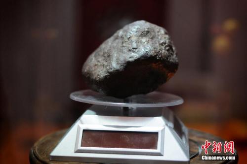 """2013年12月25日,一块约""""拳头大""""标价8千万的陨石,摆在乌鲁木齐一陨石店中央。马新龙 摄"""