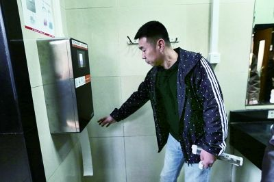 A tourist is using the face detection toilet paper dispenser in Temple of Heaven Park on Mar 18, 2017. [Photo: fawan.com]