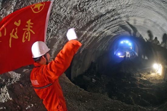 3月20日,在朝阳隧道内部,施工建设者在隧道贯通后向另一侧的工友挥手。