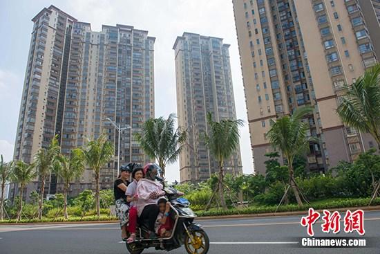 资料图:市民在海口市区某地产项目前路过。 <a target='_blank'  data-cke-saved-href='http://www.chinanews.com/' href='http://www.chinanews.com/'><p  align=