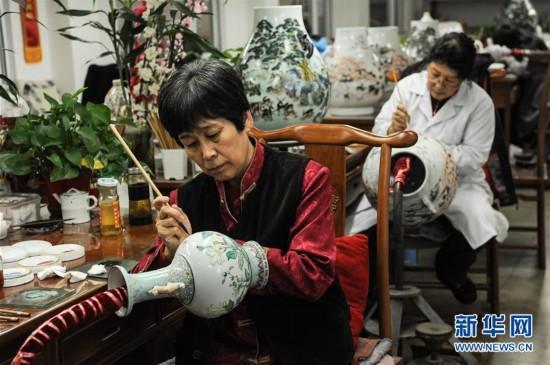 京彩瓷技艺传承人白莉(前)和同事一起创作.蒲东峰 摄