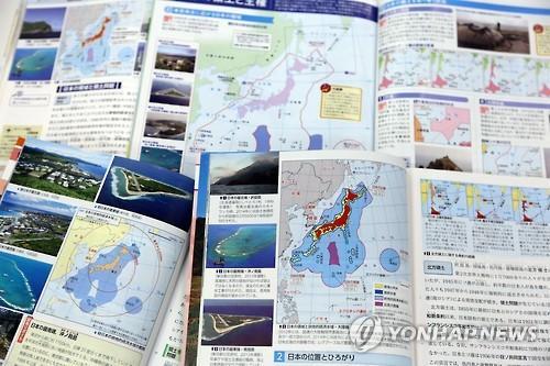 """资料图片:去年日方审定通过教科书。书中写道""""竹岛是日本固有领土,但非法占岛的韩国声称拥有其主权。""""。(图片来源:韩联社)"""