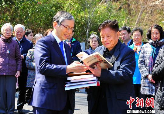图为童丹宁(图右)向马场校长赠送有关周恩来的史料书籍。 王健 摄
