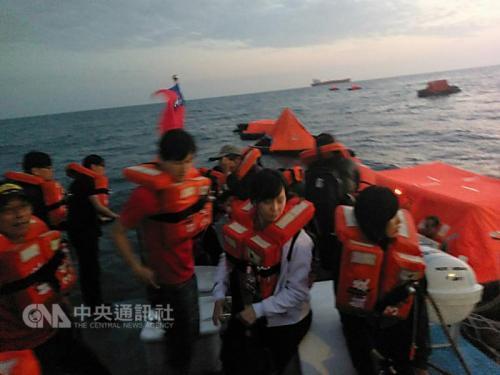 图为海巡队将乘坐救生艇的游客救上巡防艇。