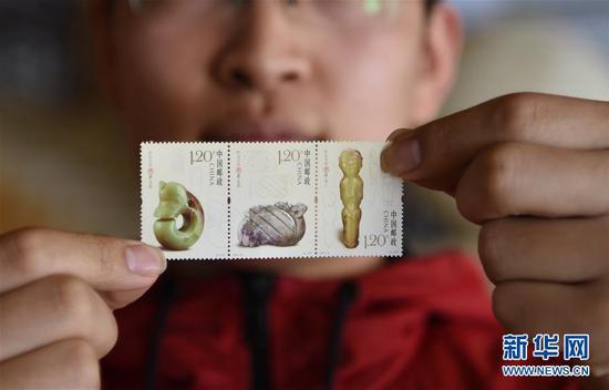 4月9日,集邮爱好者在展示《红山文化玉器》特种邮票