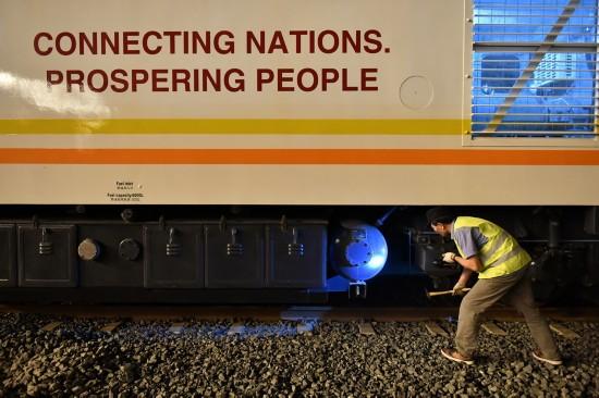 4月13日,在肯尼亚蒙内铁路内罗毕站,中方技术人员许景林进行当日测试运行后的检查工作。新华社记者孙瑞博摄