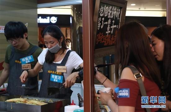 """4月14日,来自台南美食小店的业者在现场制作特色街头美食""""阿杰手工蛋饼""""。当日,由台南市观光旅游局主办的为期四天的第三届""""台南街头小食节""""在香港荷里活广场登场。 新华社记者 李鹏 摄"""
