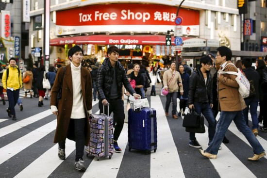 People cross a street outside a tax free department store popular among Chinese tourists in Tokyo, Japan, February 11, 2016. [Photo: Reuters/VCG]
