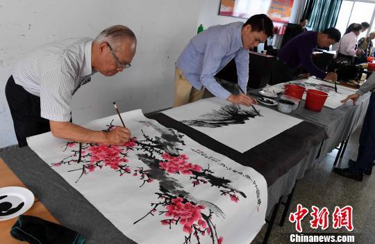 跨海前来参加此次书画艺术笔会交流活动的台中云山画会副理事长陈守信(左一)等台湾书画家现场挥毫泼墨。 记者刘可耕 摄