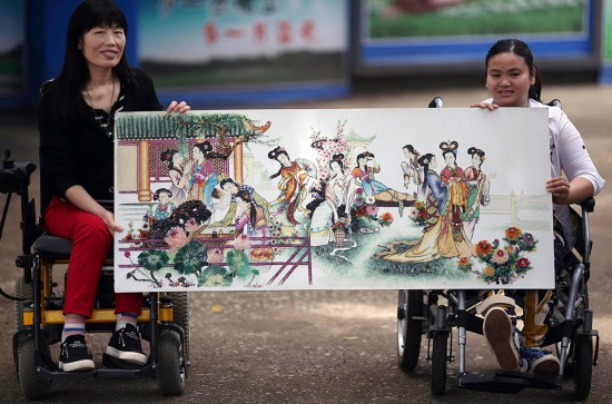 4月19日,邓凤竹(左)与她的一名学员在展示宝石画作品《金陵十二钗》。