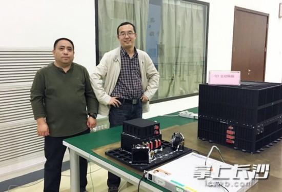 任维佳(右)与主动隔振装置电控箱和主体合影。