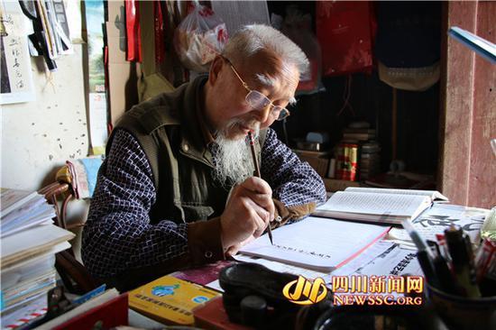 屈建功老人正在抄写古文