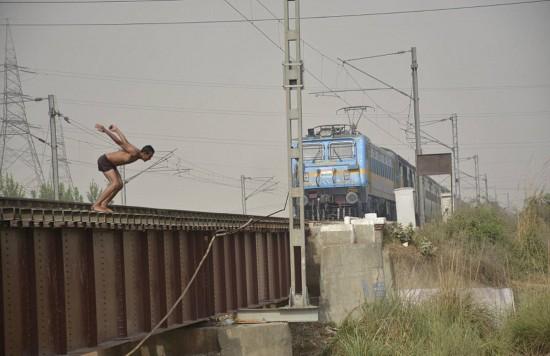 """在疾驰的火车前跳水 印度青少年冒生命危险玩""""死亡特技""""(组图)"""