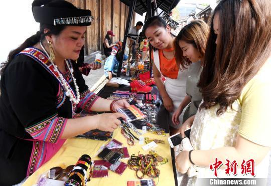 台湾少数民族手作文创艺术品吸引福州女青年眼球。 记者刘可耕 摄