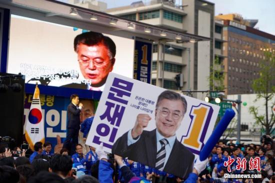 """4月17日,韩国最大在野党共同民主党总统候选人文在寅(图中)在首尔光化门广场参加竞选造势活动。韩国第19届总统选举竞选活动当日正式启动,包括国会5大党派代表在内的15名候选人将在22天的法定竞选期间奔走全国各地展开""""拉票大战""""。 <a target='_blank'  data-cke-saved-href='http://www.chinanews.com/' href='http://www.chinanews.com/'><p  align="""