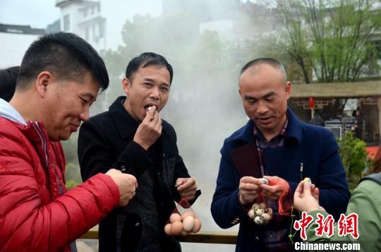 热气腾腾的温泉旁,游客品尝温泉美食。 通讯员 朱桂花 摄