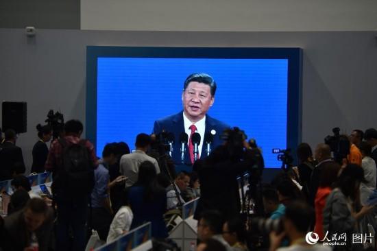 会议新闻中心记者们聚焦直播屏幕报道习近平主旨演讲。人民网 翁奇羽 摄