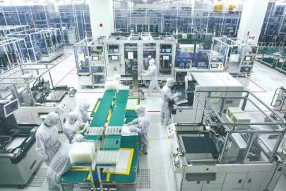遂宁市一家电子科技公司生产车间,工作人员通过放大镜检查电路板