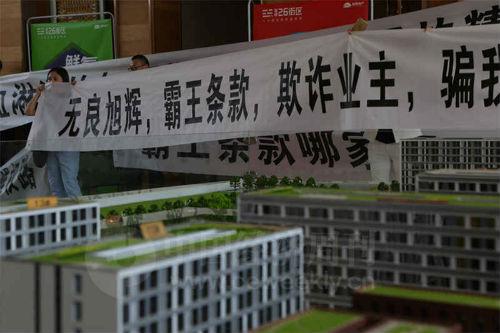 """5 月6 日,有业主自发前来""""旭辉26 街区""""维权,他们在售楼中心大厅内拉起横幅。《中国经济周刊》视觉中心摄影记者 胡巍I 摄"""