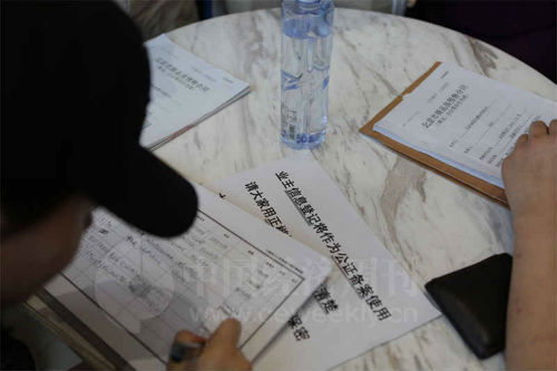 """5 月6 日""""旭辉26 街区""""售楼中心的维权活动中,业主们携带身份证、购房合同等原件,自发登记造册,方便彼此日后联络。《中国经济周刊》视觉中心摄影记者 胡巍I 摄"""