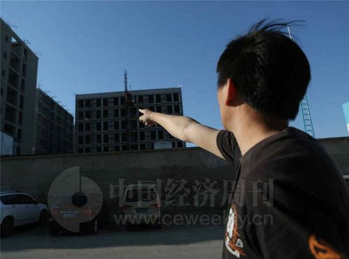 """5 月5 日,在正在建设中的""""旭辉26 街区""""工地旁,一位业主指着自己购买的房子,他担心将来建好的房子没有上下水等配套设施。《中国经济周刊》视觉中心摄影记者 胡巍I 摄"""