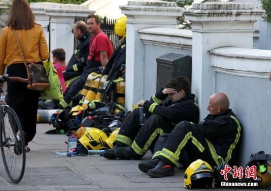 6月14日,伦敦西部一栋24层的公寓楼发生大火,火势猛烈,蔓延到了所有楼层。目前这场火灾已造成超过50人受伤。图为疲惫的消防员在路边休息。 <a target='_blank'  data-cke-saved-href='http://www.chinanews.com/' href='http://www.chinanews.com/'><p  align=