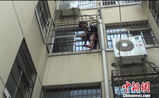 女子不慎悬空反锁防盗窗内消防员攀楼施救