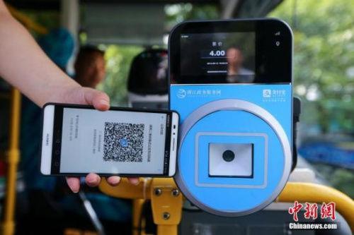 资料图:民众乘坐交通工具出行时使用手机支付。中新社发 许康平