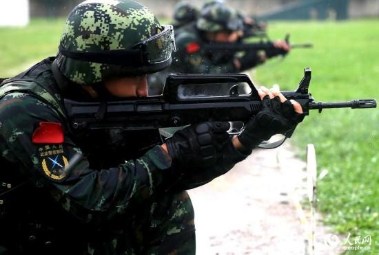 特战队员在雨中展开步枪快速精度射击。