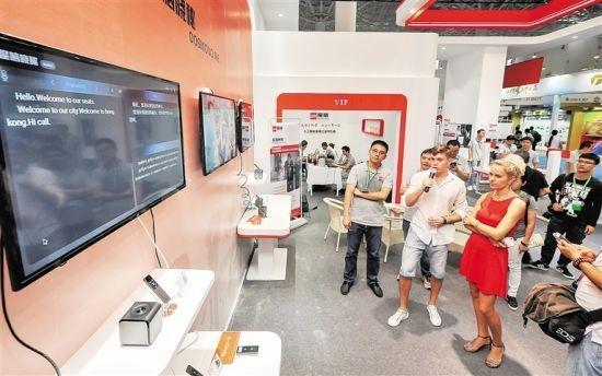 6月28日,2017海南高新技术产业及创新创业博览会上,外国嘉宾体验人工智能语音记译系统,说英文立刻同步翻译为中文。袁琛 摄