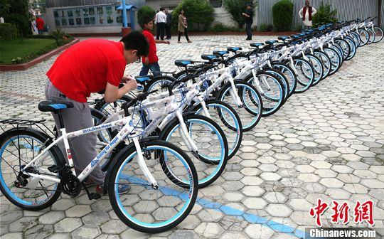 """7月1日,一位中国员工调试首批山地自行车。""""佛国单车――尼泊尔山地居民出行援助计划""""项目发布会暨捐赠仪式当日在尼泊尔首都加德满都举行。在该项目下,尼泊尔民众将获赠来自中国的三万余辆山地自行车。<a target='_blank'  data-cke-saved-href='http://www.chinanews.com/' href='http://www.chinanews.com/'><p  align="""