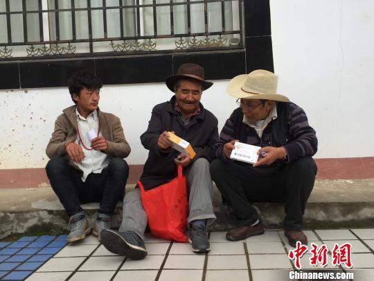 村民坐在診室外的台階上高興地給朋友介紹剛拿到免費藥品。 趙玉芹 攝
