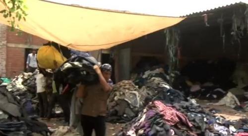 工人将衣服分类、处理后,放入粉碎机粉碎,然后制成纱线。